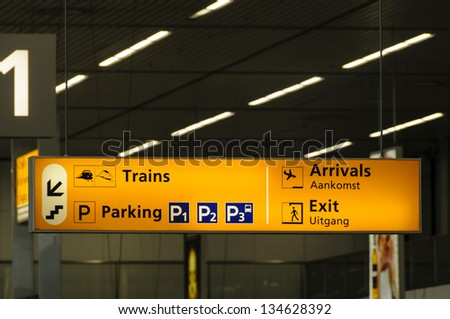 Information sign in Schiphol airport in Amsterdam, Nederlands written in English and Dutch - stock photo
