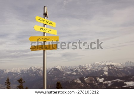 information street sign showing popular travel destinations of the world on the blurred mountain background. selective focus - stock photo