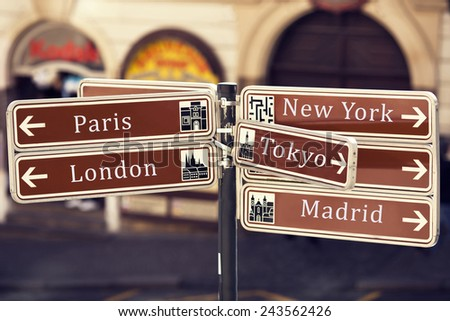 information street sign showing popular travel destinations of the world on the blurred street background - stock photo