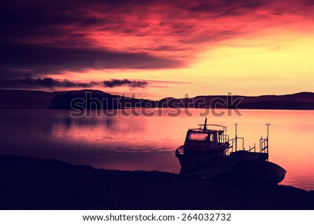 infrared colorful sunrise landscape with boat and lake, red dominant colors, filtered style   - stock photo