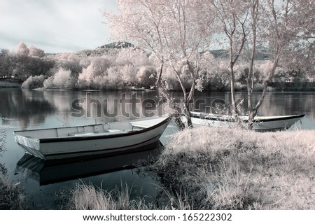 Infrared river landscape seeing boats, trees and plants - stock photo