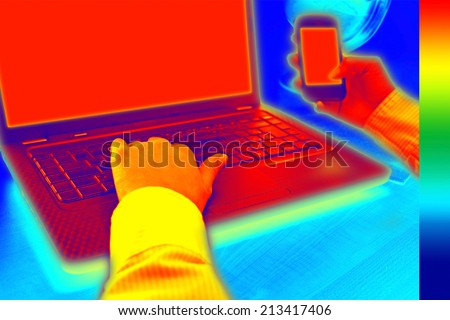 Infrared thermography image showing the heat and radiation of Notebook and smartphones in the office - stock photo