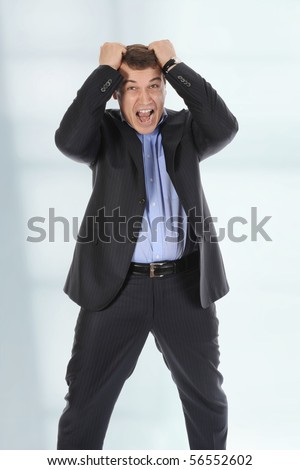 Infuriated businessman holding his head in a bright office - stock photo