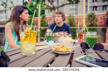 Infused fruit water cocktails and green vegetable smoothies over a table with group of young people talking in the background. Selective focus on lemon and orange water cocktail. - stock photo
