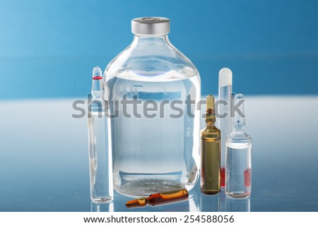 infusion bottle and medication vial on the blue background - stock photo
