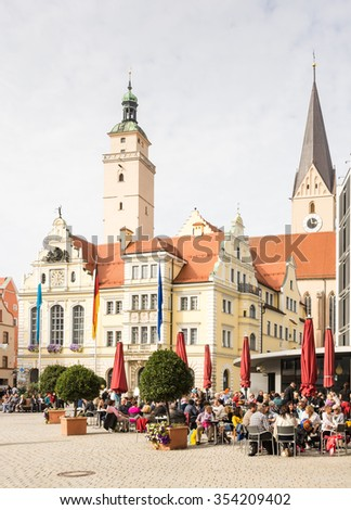 INGOLSTADT, GERMANY - OKTOBER 3: Tourists in a cafe in front of the historic town hall of Ingolstadt, Germany on Oktober 3, 2015. Foto taken from Moritzstrasse with view to the town hall. - stock photo