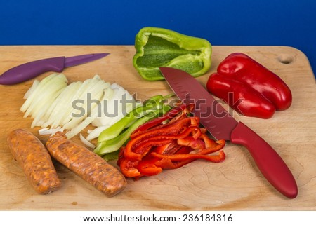 Ingredient for sausage panini being prepared on wooden cutting board. Colorful kitchen knives on blue background with copy space. - stock photo