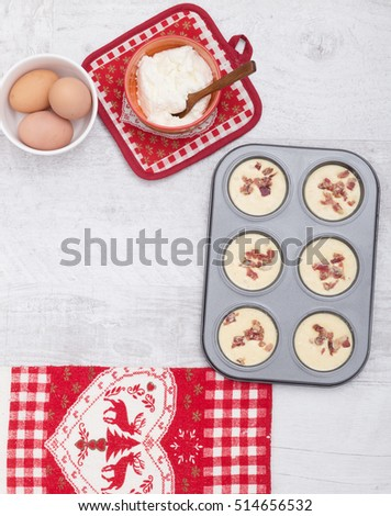 Ingredients and devices for preparation of muffins on a wooden background