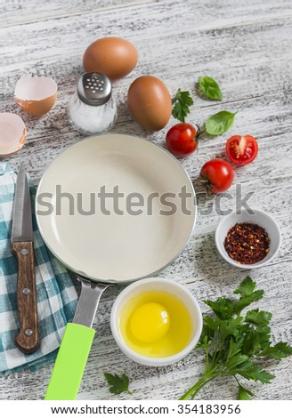 Ingredients and utensils for cooking fried eggs with tomatoes: eggs, tomatoes, spices, herbs and  pan on a white wooden table - stock photo