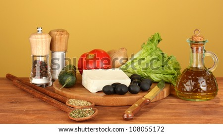 Ingredients for a Greek salad on brown background close-up - stock photo