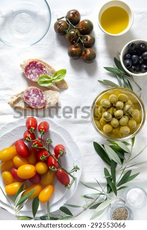 ingredients for a summer snack. summer products.sandwich with salami, red and yellow cherry tomatoes, green and black olives, black Sicilian tomatoes, bread sticks and olive oil. - stock photo