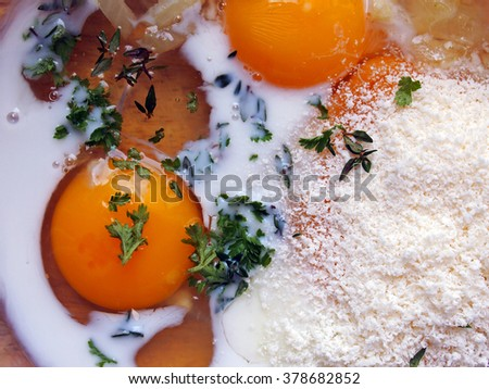 Ingredients for a traditional Italian omelette (frittata) in a bowl: eggs, herbs, milk, Parmesan cheese, onions. - stock photo