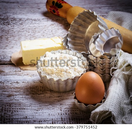 Ingredients for backing  cupcakes: egg, flour, butter. Selective focus, toned - stock photo