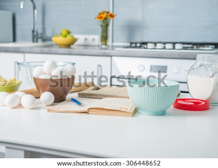 ingredients for baking and recioe book on a kitchen table - stock photo