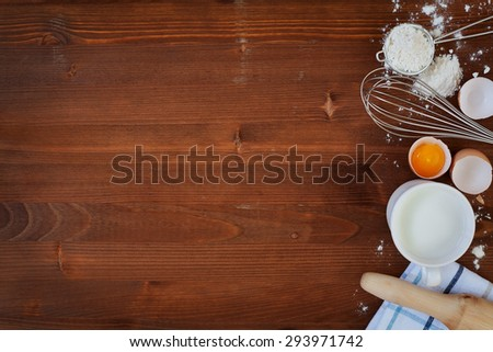 Ingredients for baking dough including flour, eggs, milk, whisk and rolling pin on wooden rustic background, empty space for text, top view, toning - stock photo