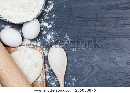 Ingredients for baking dough including flour, eggs, milk, whisk and rolling pin on wooden rustic background, empty space for text, top view - stock photo