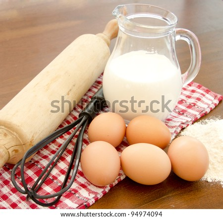 ingredients for baking: eggs, flour, milk jug, rolling pin, whisk, napkin - stock photo