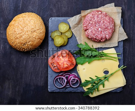 Ingredients for burger: raw cutlet, tomato, cheese, onion. Selective focus - stock photo