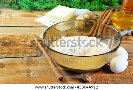 Ingredients for christmas cookies (flour, eggs, spices, honey, butter) and christmas tree branches on background