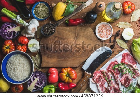 Ingredients for cooking dinner. Raw uncooked lamb meat chops, rice, oil, spices and vegetables over wooden background, top view, copy space - stock photo