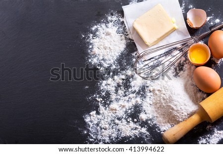 ingredients for cooking: flour, butter, eggs on dark background - stock photo