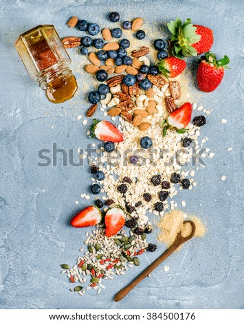 Ingredients for cooking healthy breakfast.  Strawberries, blueberries, nuts, oat flakes, dried fruits, honey with drizzlier over concrete textured background, top view,vertical - stock photo