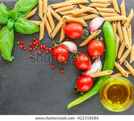 Ingredients for cooking Italian cuisine - pasta, tomatoes, garlic, Basil, hot pepper, olive oil and spices. Top view . Copy space - stock photo