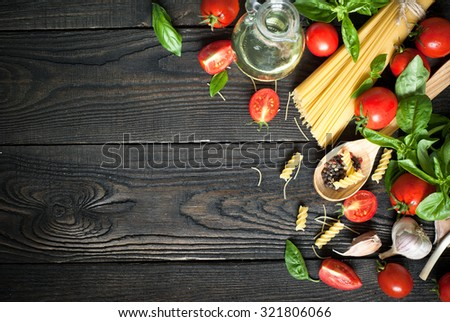 Ingredients for cooking Italian pasta - spaghetti, tomatoes, basil and garlic. Top view, copy space. - stock photo