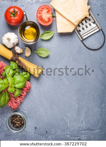 Ingredients for cooking pasta Bolognese. Spaghetti, Parmesan cheese,  tomatoes, metal grater, oil, garlic, minced meat, pepper and basil on grey concrete background, top view, copy space, vertical - stock photo