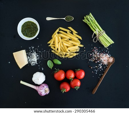 Ingredients for cooking pasta. Penne, green asparagus, basil, pesto sauce, garlic, spices, parmesan cheese and  cherry-tomatoes on dark grunge backdrop, top view - stock photo