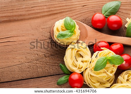 Ingredients for cooking pasta. Raw tagliatelle, basil and tomatoes on the rustic wooden background, top view - stock photo