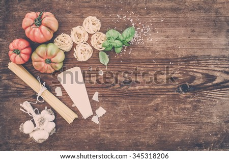 Ingredients for cooking pasta. Spaghetti, olive oil, garlic, Parmesan cheese, tomatoes and fresh basil on black slate background, top view, copy space. Pastel tone - stock photo