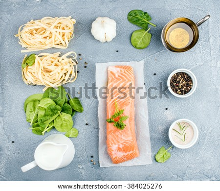 Ingredients for cooking pasta tagliatelle with salmon, spinach and cream on grey concrete textured background, top view - stock photo
