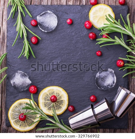 Ingredients for cranberry cocktail with lemon and rosemary on a black stone top view of the board with ice cubes and cocktail metal cups. selective Focus - stock photo