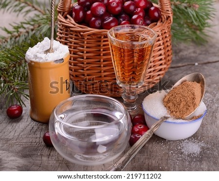 ingredients for cranberry sauce organic wild cranberries in wicker basket starch, winewater, cinnamon, sugar on wood  - stock photo