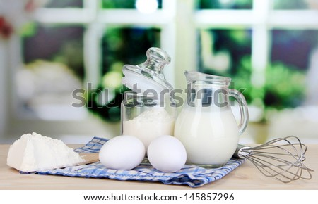 Ingredients for dough on wooden table on window background - stock photo