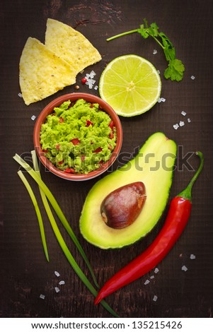 Ingredients for guacamole and guacamole dip on a dark background. - stock photo