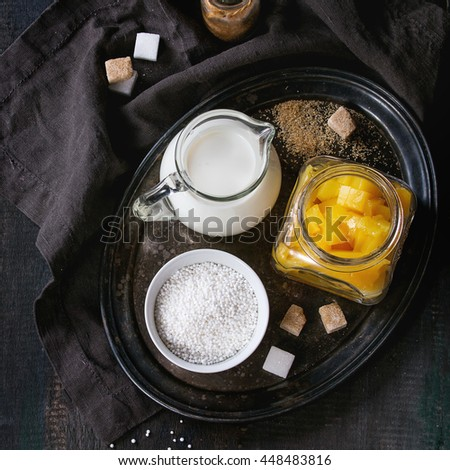 Ingredients for healthy tapioca pearls pudding dessert with coconut milk and mango. Served on vintage iron tray over wooden table with black textile napkin. Dark rustic style, flat lay. Square image - stock photo