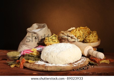 ingredients for homemade pasta on wooden table on brown background - stock photo