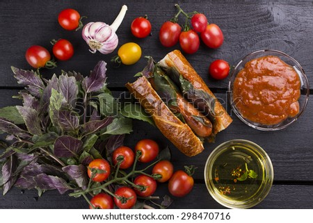Ingredients for hot dog: cherry tomatoes, garlic, basil, ketchup, oil on wooden background. Top view - stock photo