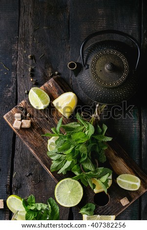 Ingredients for ice green tea lime, lemon, mint, sugar, green tea and ice cubes on wooden chopping board with cocktail glass and black iron teapot over old wooden background. Flat lay - stock photo