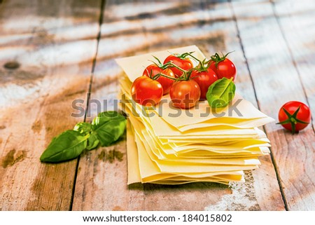Ingredients for Italian lasagne with fresh cherry tomatoes and green basil leaves on sheets of dried pasta on a rustic wooden kitchen table - stock photo