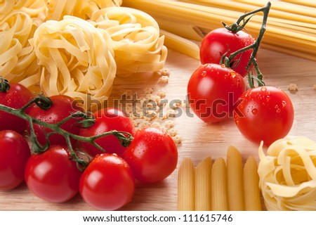 Ingredients for Italian pasta with a bunch of ripe red cherry tomatoes and noodles for tagliatelle or fettuccini with tiny stelline pasta usually used in soups - stock photo