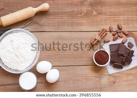 Ingredients for making chocolate chip cookies on a wooden background . Flour , sugar, egg , cocoa , cinnamon , vanilla and butter. Close up. Top view - stock photo