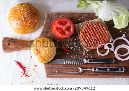 Ingredients for making homemade burger on wooden cutting board, served with meat fork and knife over White tablecloth. Dark rustic style. Top view - stock photo