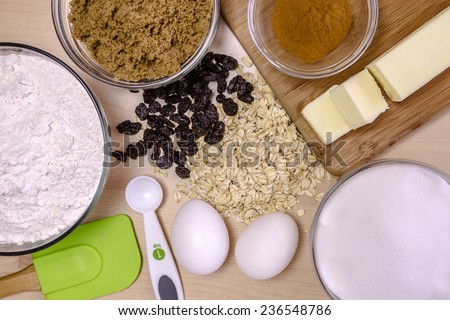 Ingredients for making homemade oatmeal raisin cookies with green spatula and white spoon - stock photo