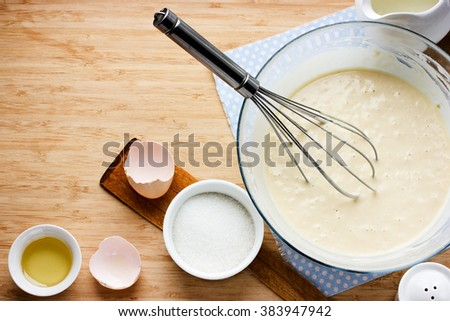 Ingredients for making pancakes - egg, butter, milk, sugar and raw dough for pancakes on wooden background. Rustic or rural style. Top view with free text space - stock photo