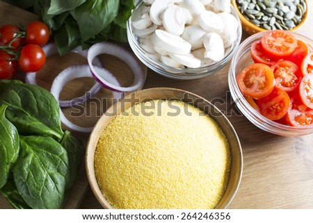 Ingredients for polenta recipe, with polenta in wooden bowl with sliced tomatoes, spinach and red onions. - stock photo