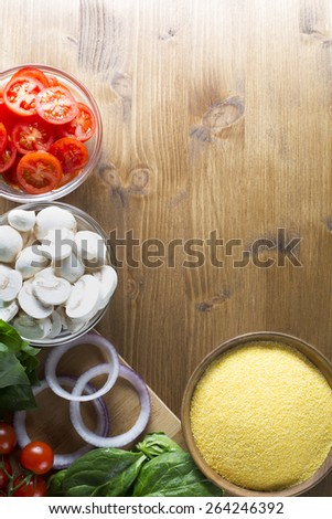 Ingredients for polenta recipe, with polenta in wooden bowl with sliced tomatoes, spinach and red onions.  Viewed from angle directly above with copy space on wooden table.  vertical or horizontal - stock photo