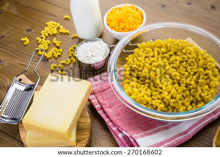 Ingredients for preparing macaroni and cheese on a wood table. - stock photo